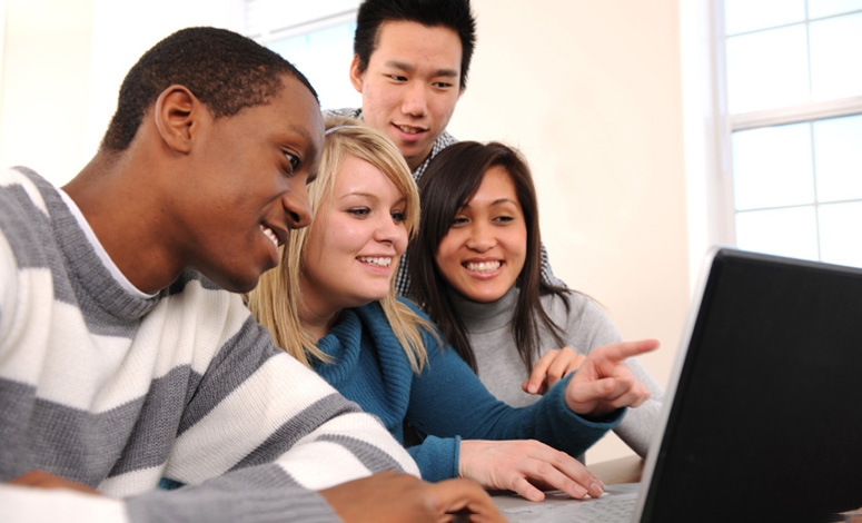 group of students gathered around a laptop