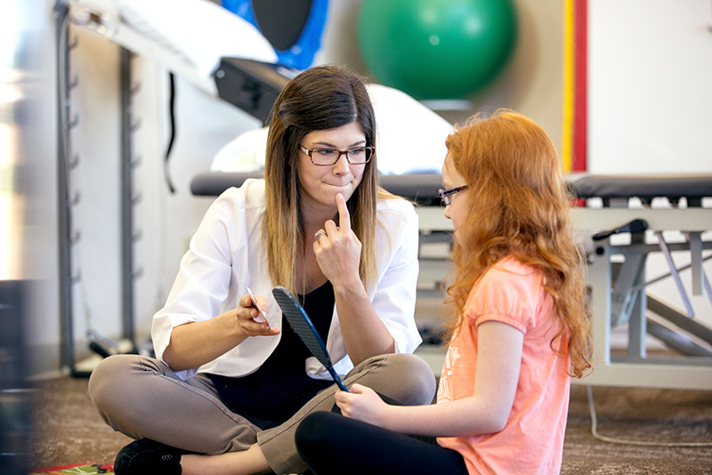 Speech language pathologist with child