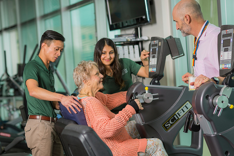 SHP students helping woman use exercise equipment