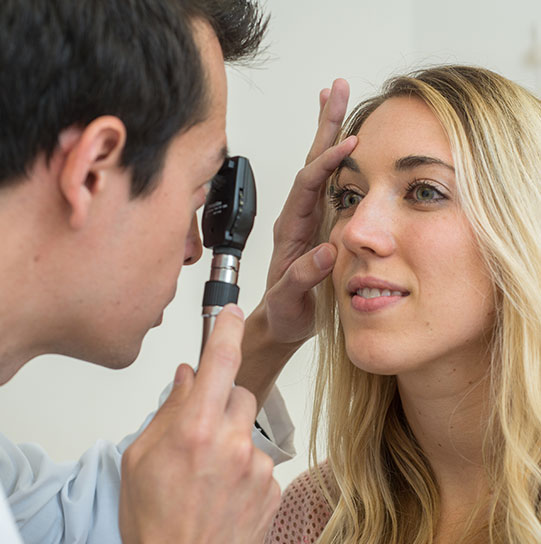 Physician assistant checking eyes of patient