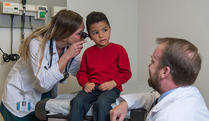 Allied health professional examining child's ear.