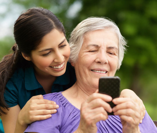 Smiling woman and daughter looking at mobile device