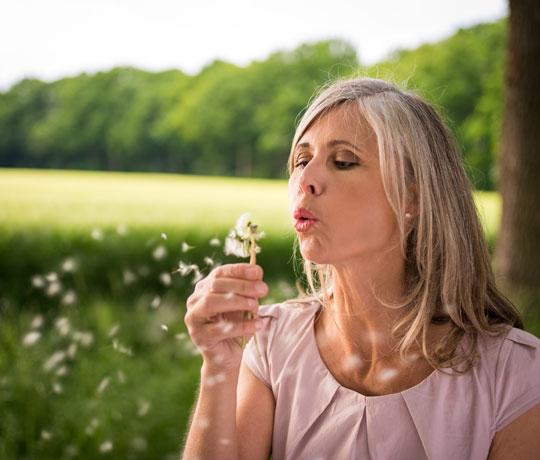 Woman blowing daffodil