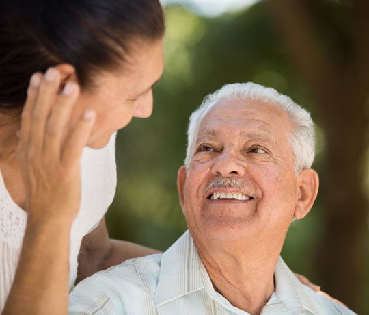 Elderly man smiling at daughter