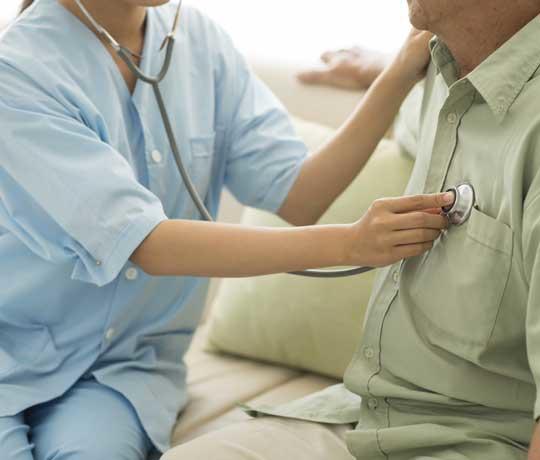 Nurse listening to patient's heart
