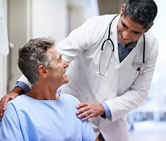 Physician talking to mature male patient