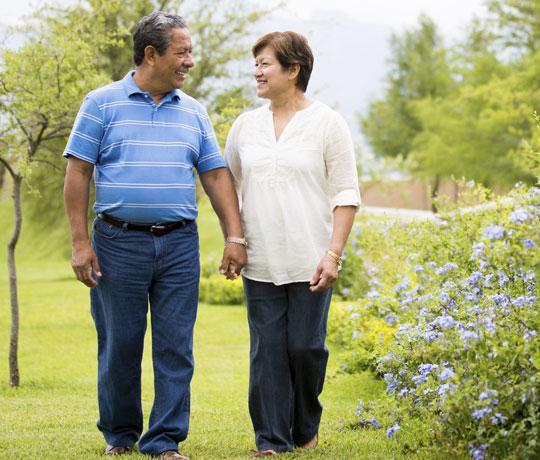 Happy couple walking through garden