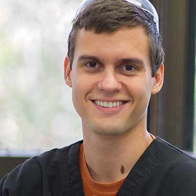 Endodontics dental resident in scrubs, smiling.