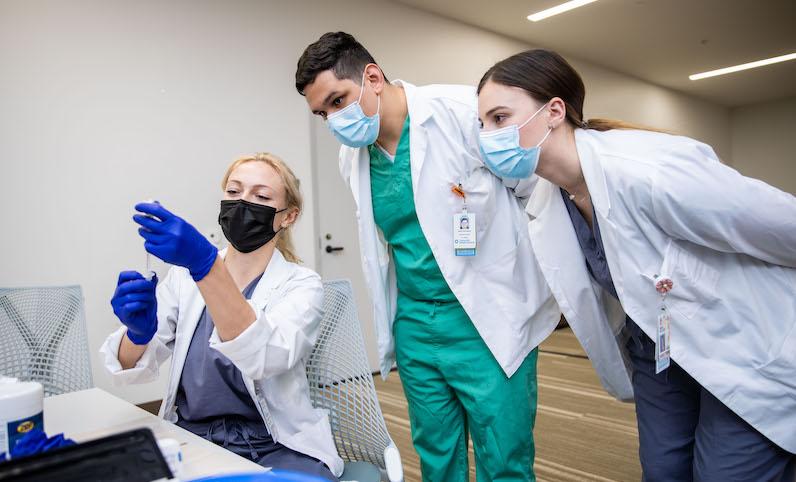 Medical students examine COVID vaccine