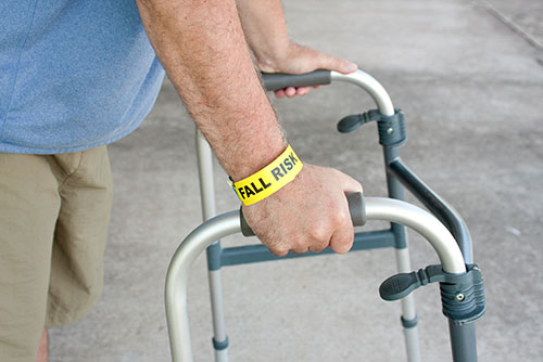 Patient using walker with fall risk bracelet on