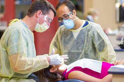 Dentists checking teeth of ceramic dental implant candidate