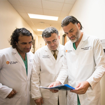Cardiologist S. Hinan Ahmed, vascular surgeon Mark Davies, and podiatrist Thomas Zgonis share notes on a patient