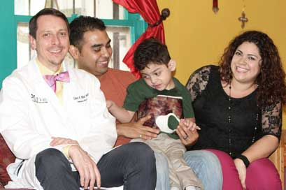 Dr. Medellin and young male patient with family. Dr. Glen Mendellin treats pediatric special-needs patients.