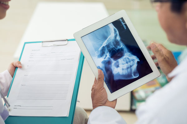 Oral and maxillofacial surgeon reviewing a patient's facial x-rays