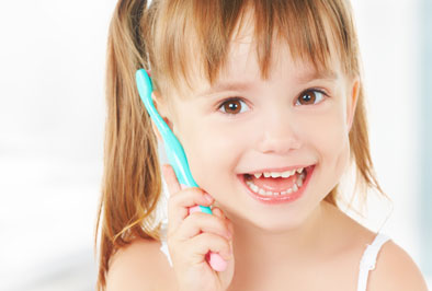 young child holding a toothbrush