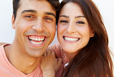A man and woman smiling and showing their clean teeth