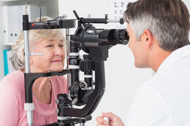 Eye doctor conducting eye exam on a patient