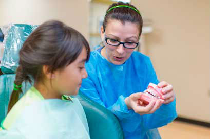 A pediatric dentist in San Antonio shows a child how to care for her teeth.