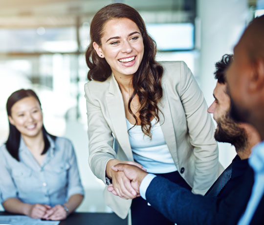 Professional woman shaking hands with coworker