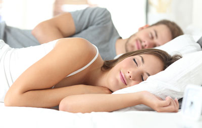 Couple sleeping soundly, free of sleep disordered breathing.