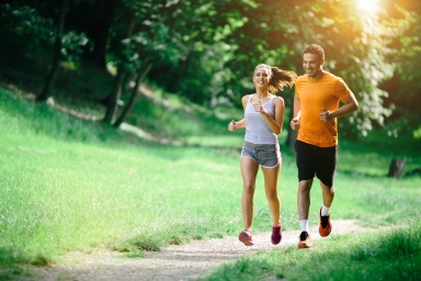 male and female couple running down a path