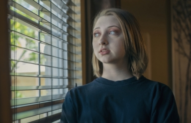 Stressed teen looking out window