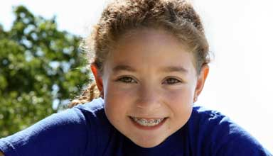 Happy dental patient with traditional braces and orthodontics. An orthodontist will straighten teeth with affordable braces or Invisalign braces.