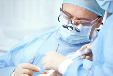 Oral surgeon performing surgery on a dental patient