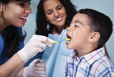Pediatric dentist performing a checkup on a young dental patient